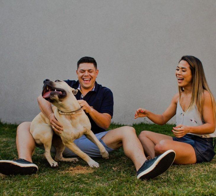Pareja de novios sentados en el pasto mientras rien y juegan con su perro