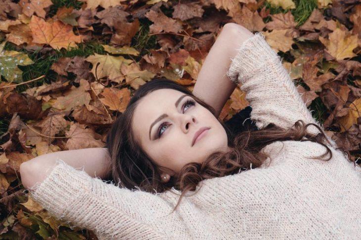 Mujer joven acostada sobre las hojas caídas de los árboles pensando
