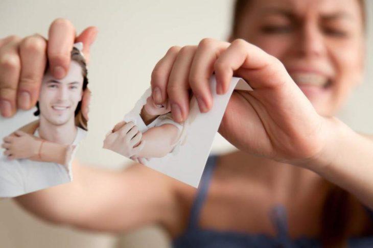 Mujer rompiendo fotografía luego de ruptura amorosa