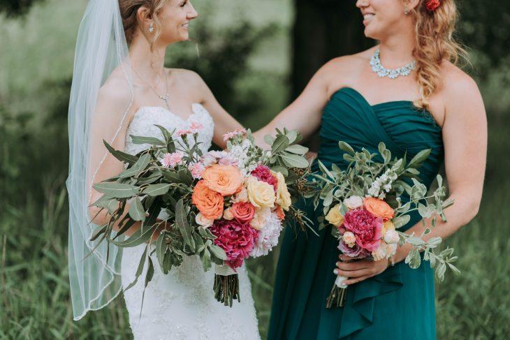 Novia y su dama de honor sosteniendo un ramo de rosas