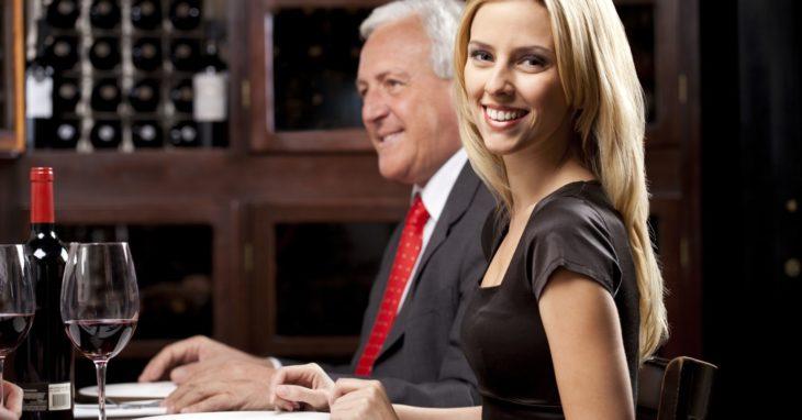Mujer joven en una cena con un hombre mayor