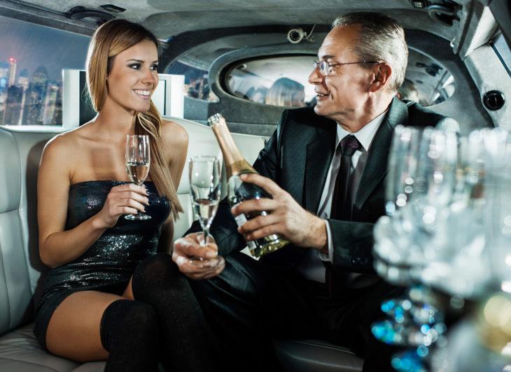 Mujer joven y hombre mayor tomando una copa de vino