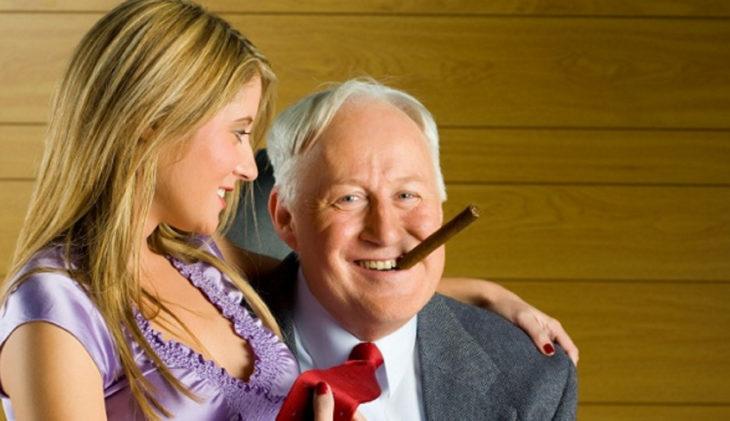 Mujer joven sentada en las piernas de un hombre mayor que fuma un puro