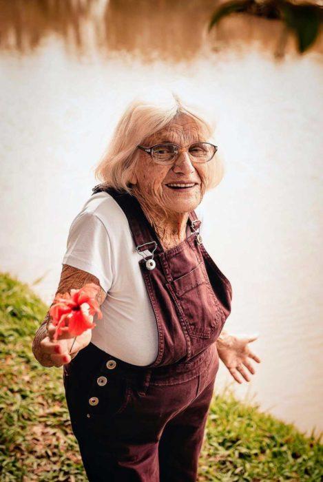Claire V. a la orilla de un lago muestra una flor