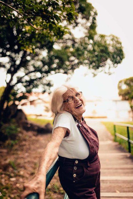 Claire V. recargada sobre un pasamanos con el fondo de una vereda en un parque y árboles
