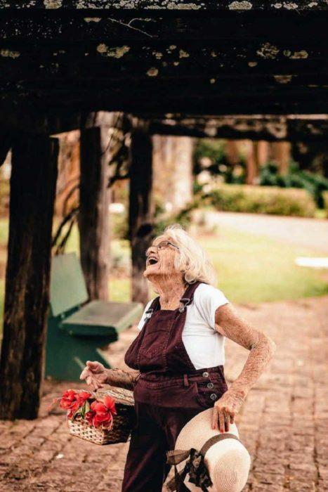 Claire V. una mujer de 90 años camina por un parque con una canasta de flores y ríe a carcajadas
