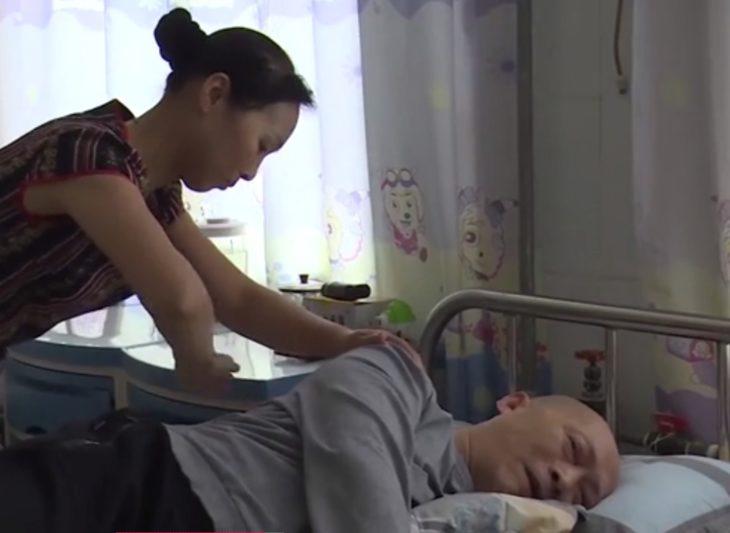 Esposa de Li Zhihua le da masaje en la espalda mientras él está acostado en la cama del hospital