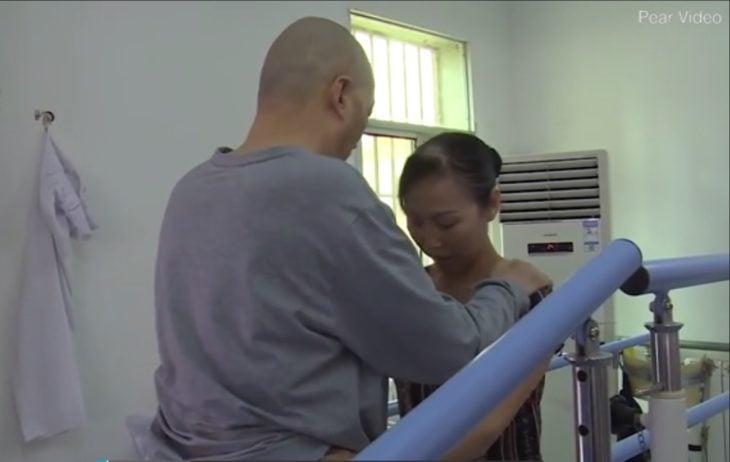 Esposa de Li Zhihua lo sostiene mientras él va a dar un paso