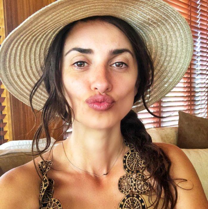 Penélope Cruz con un sombrero y una trenza, envía un beso