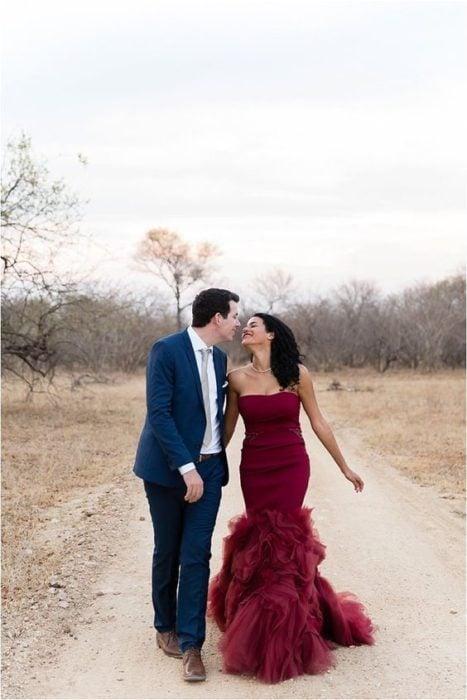 Una pareja de novios camina por un paraje de campo amarillento, ella viste vestido rojo quemado