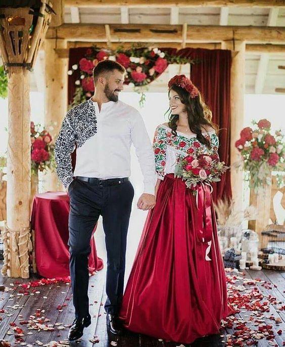 una pareja de novios él vestido de camisa blanca con pantalón oscuro y ella con blusa bordada y falda roja