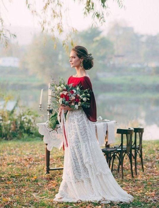 una novia con un vestido blanco y rojo a un lado de una mesa decorada cerca de un lago en el campo