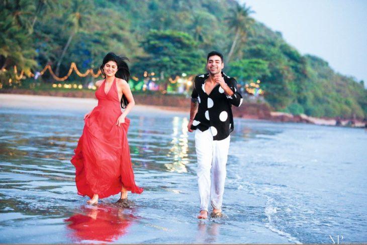 una pareja va corriendo por la playa, él con camisa negra con blanco y pantalón blanco y ella con vestido rojo