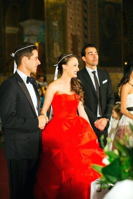 Una pareja de novios y su padrino frente al altar, ella viste vestido rojo estrapless y moño blanco en la cabeza