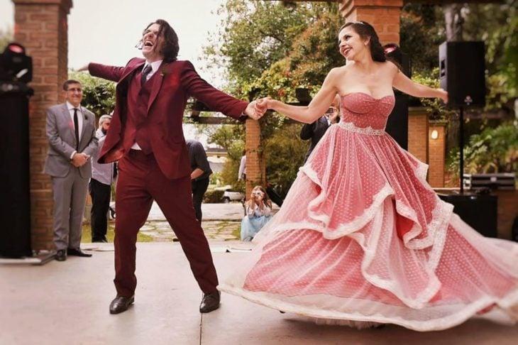 Una pareja de novios baila en una pista, ella con vestido rojo con gasa blanca encima