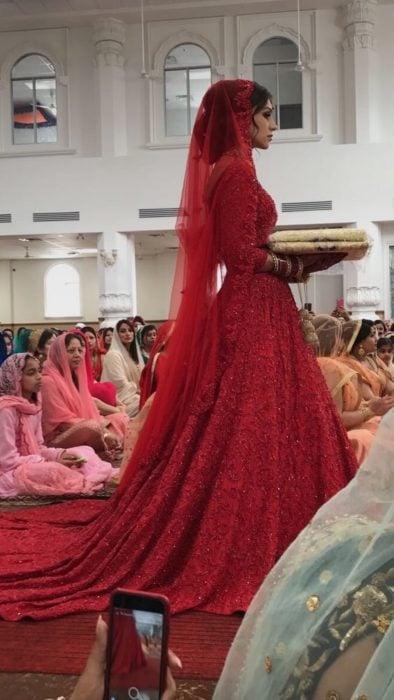 Una novia hindú con vestido rojo camina hacia el altar en un templo lleno de personas sentadas en el piso