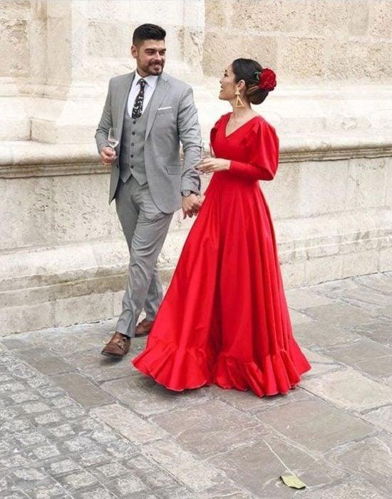 Pareja camina por una calle, él vestido de gris y ella con vestido rojo estilo 'sevillano'