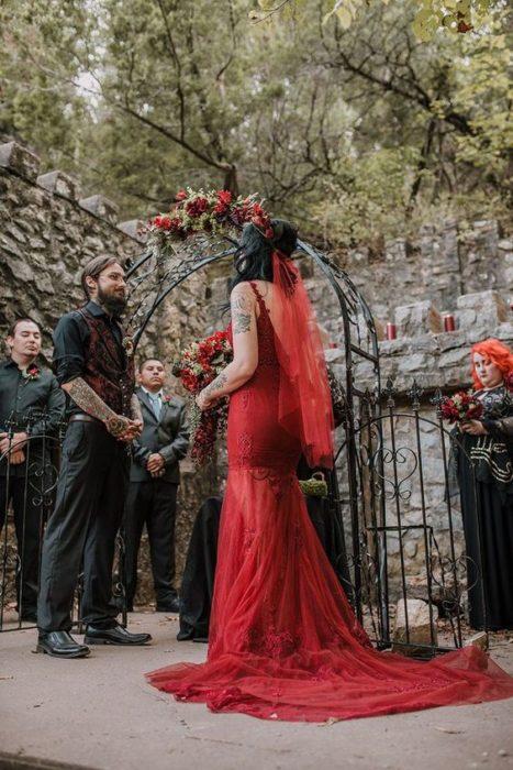 una pareja de novios se casa en un jardín, ella con vestido rojo entallado y velo rojo