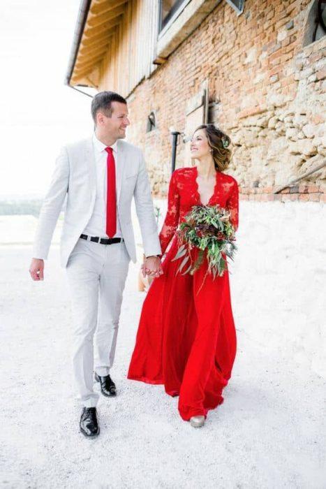 Una pareja tomada de la mano camina a un lado de un edificio de piedra, él con traje gris y corbata roja y ella vestido rojo y con su ramo
