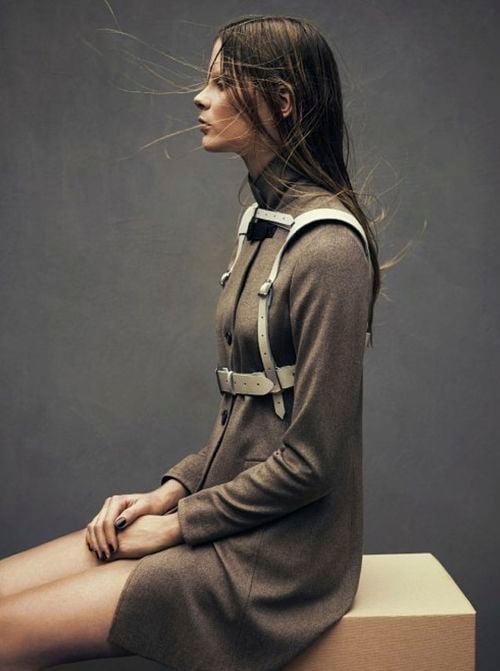 una mujer sentada con un abrigo gris y un arnés de piel sobre él