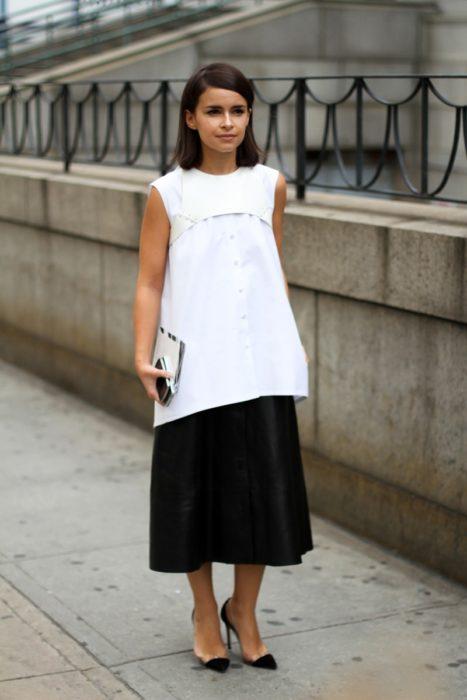 Una mujer vestida de falda larga negra y maxi blusa blanca con un arnés blanco encima