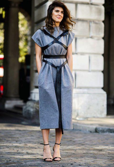 una mujer con vestido gris largo usa un arnés de piel sobre su pecho y anudado a la cintura