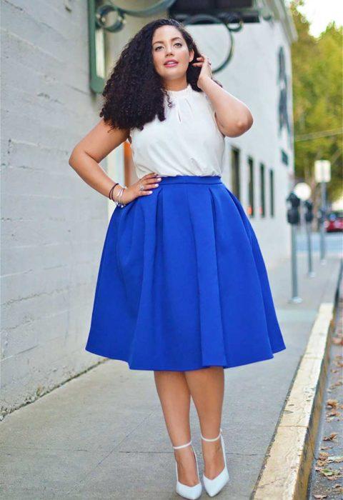 mujer caminando sobre una banqueta vestida con falda azul rey y con blusa blanca