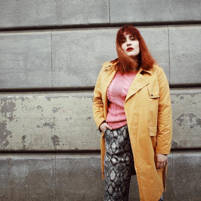 Una mujer posa frente a una pared de concreto con un pantalón de animal print, un suéter rosa y una gabardina amarilla