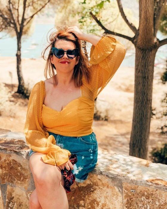 una mujer sentada en una bardita en un paraje natural, vestida con short de mezclilla y blusa mostaza y lentes de corazón