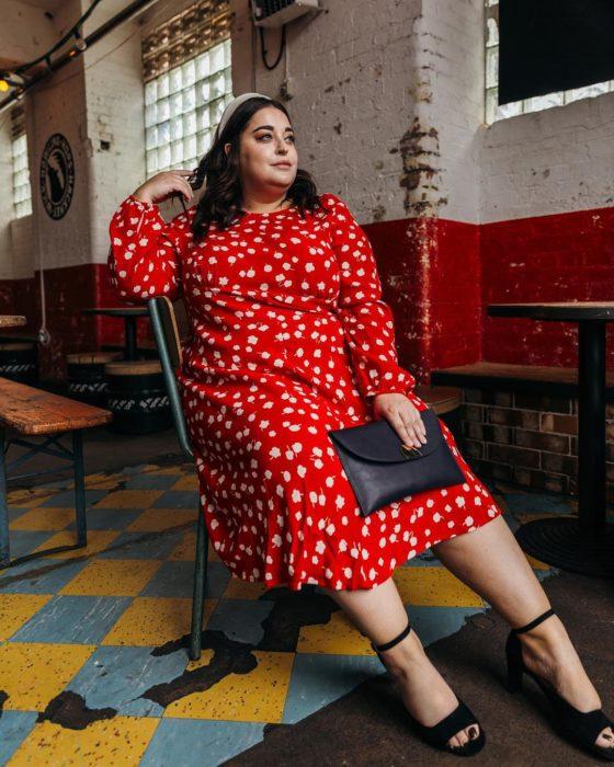 Mujer con un vestido rojo y detalles blancos sentada, tiene una bolsa de sobre negra en la mano