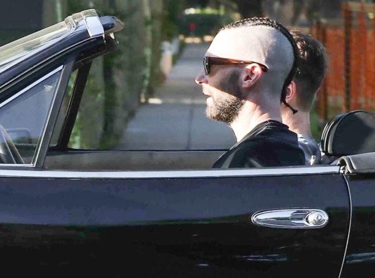 Adam Levine conduciendo un auto deportivo con quema cocos