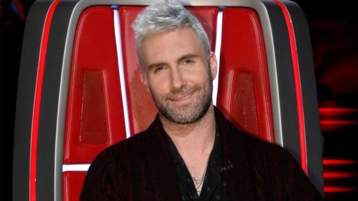 Adam Levine sentado en una silla roja en el programa The Voice