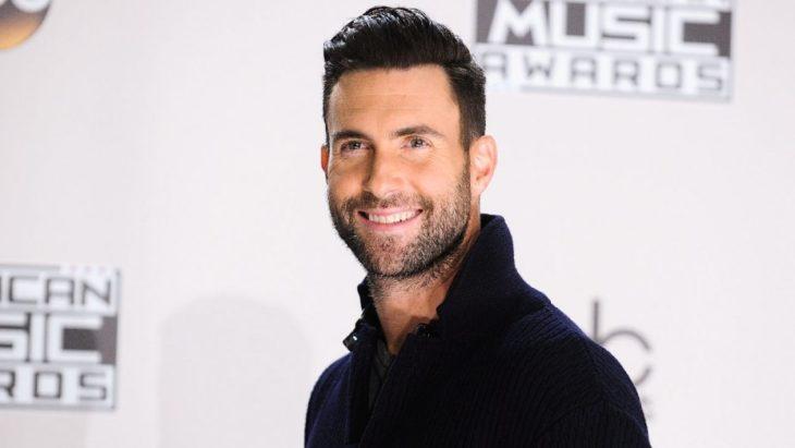 Adam Levine sonriendo en una alfombra roja