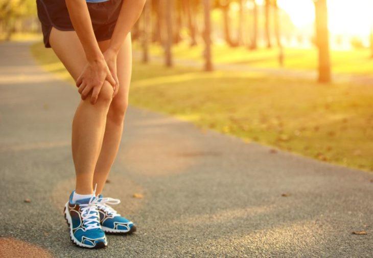 las piernas de una mujer con el fondo de un parque, ella se toca la rodilla en señal de dolor