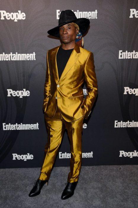 Billy Porter con traje amarillo y tacones negros
