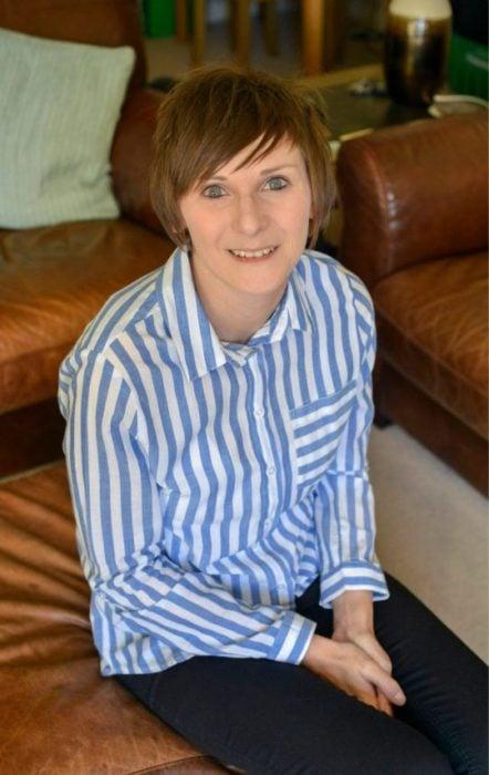 Emma Burrows en remisión sentada en un sofá con blusa azul y blanca