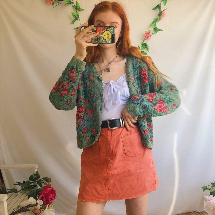 Outfits con cardigans; chica pelirroja con falda color salmón y suéter tejido con botones y flores, estilo abuelita