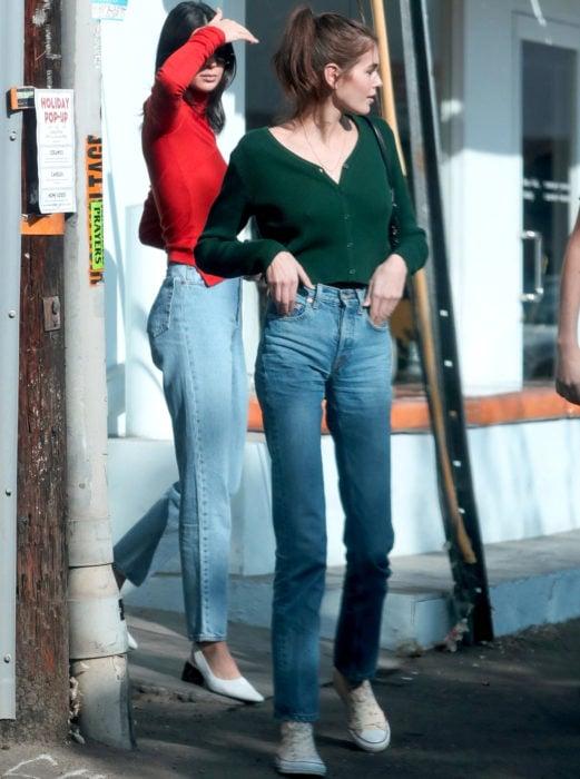 Outfits con cardigans; Kaia Gerber con suéter verde de botones y mom jean con converse color hueso