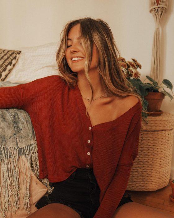 Outfits con cardigans; chica rubia sonriendo, vestida con suéter rojo de botones, con hombro descubierto