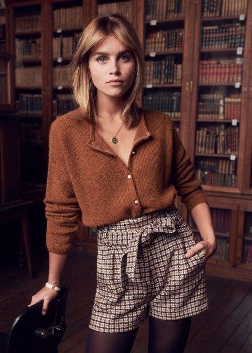 Outfits con cardigans; mujer de cabello rubio corto a los hombros, vestida con suéter café de botones y short de cuadros, en una biblioteca