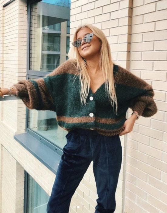 Outfits con cardigans; chica rubia sonriendo con suéter oversized tejido de botones, color verde y café