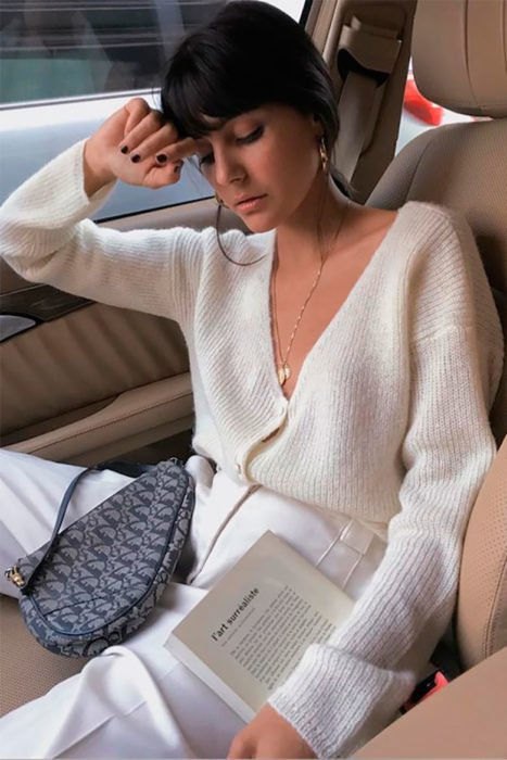 Outfits con cardigans; chica con suéter de botones blanco con libro en la mano