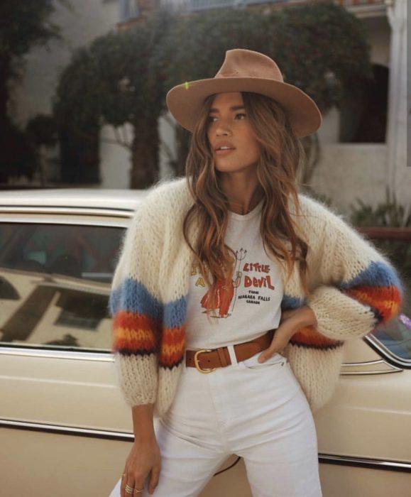 Outfits con cardigans; chica con estilo bohemio, con suéter tejido de botones, blanco con rayas azules y rojas, pantalón blanco y sombrero vaquero