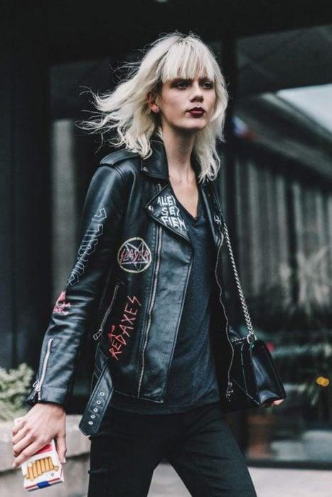 Chica rubia con chaqueta de cuero negra con logos de bandas de rock