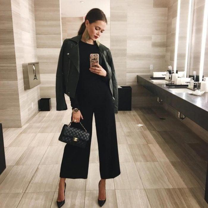 Mujer peinada con coleta lacia, vestida con traje negro y chamarra de cuero negra, tomándose una selfie en el espejo del baño