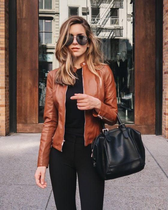 Mujer rubia castaña, con lentes de sol, bolsa negra y chaqueta de cuero marrón-anaranjada