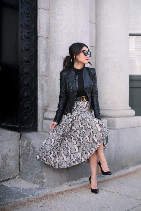 Mujer sentada afuera de edificio usando lentes grandes de sol, chaqueta de cuero negra y falda larga de animal print de serpiente