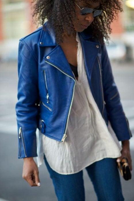 Chica morena de cabello afro con chaqueta de cuero azul rey