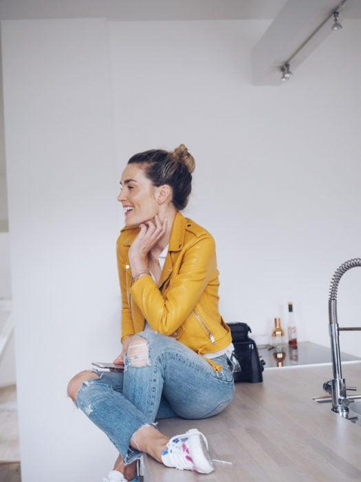 Chica sentada en barra en la cocina, con peinado de chongo, vistiendo chaqueta de piel amarilla y pantalón de mezclilla desgastado