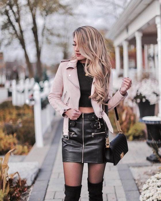 Muchacha de cabello largo y rubio, con chaqueta rosa de cuero y falda negra con hebillas